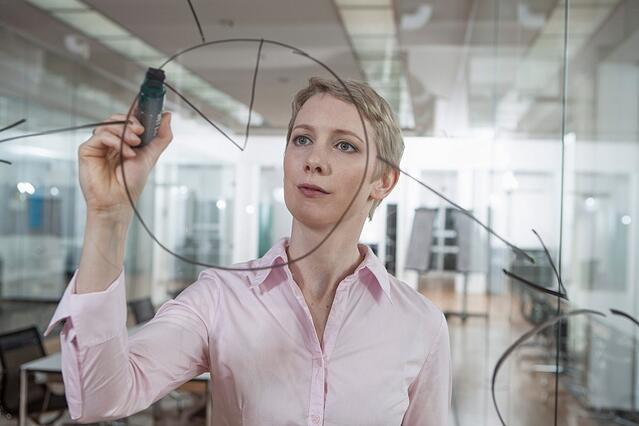 Nainen kirjoittaa läpinäkyvälle taululle