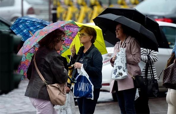 Kolme naista sateenvarjon kanssa kadulla