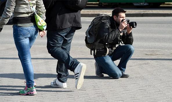 Valokuvaaja kyykistynyt kadulla
