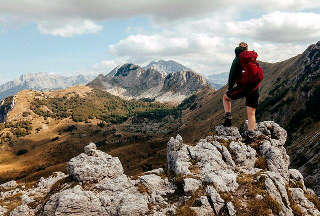 Henkilö seisoo vuorella