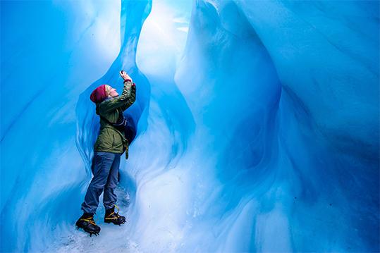 Nainen valokuvaa jääluolassa