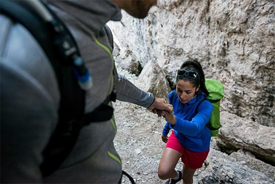 Mies auttaa naista kiipeämään