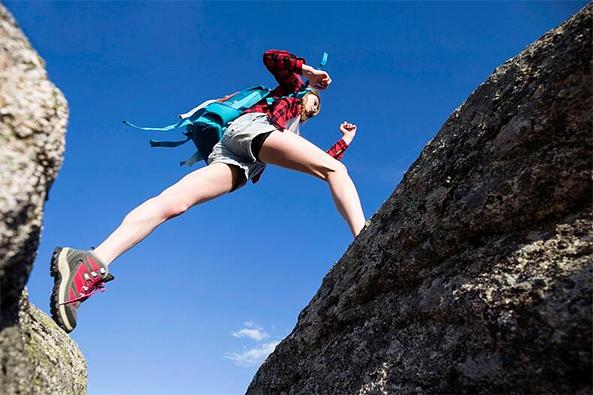 Nainen hyppää kalliolla